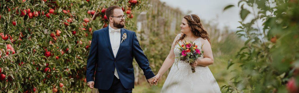 Brautpaar läuft Hand in Hand durch ein Feld mit rot leuchtenden Apfelbäumen